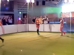 Sporty women play indoor soccer for audience